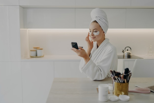 Young attractive woman in bathrobe and towel turban on head applying cosmetic patches under eyes from dark circles, looking in compact mirror and smiling while standing in modern kitchen at home
