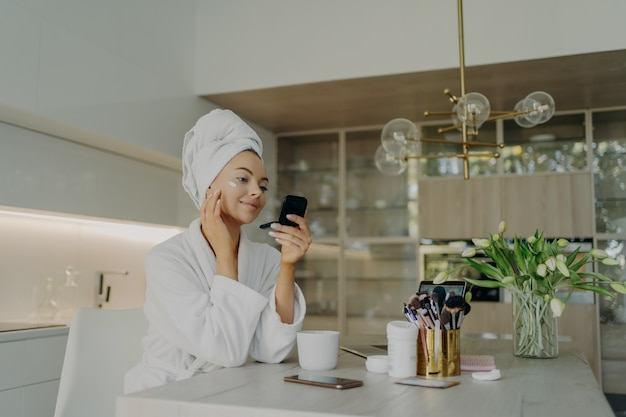 Young attractive woman in bathrobe with hair wrapped in towel applying cosmetic cream on face and looking in compact mirror, doing cosmetic procedures for skin while sitting in modern kitchen at home