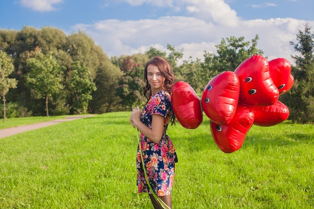 Young attractive woman in beautiful dress with red balloons walking outside