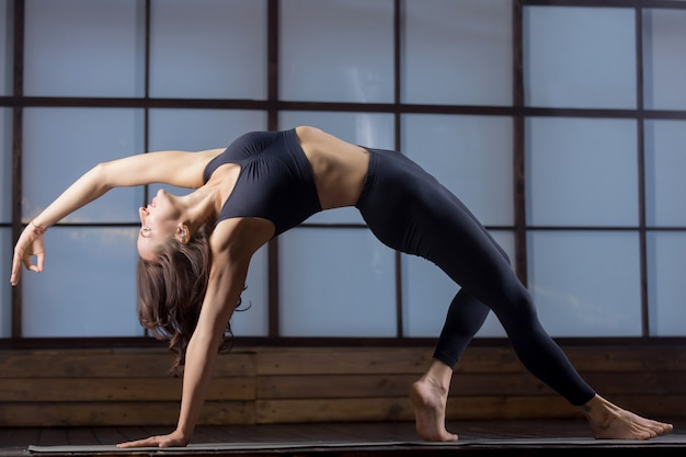 Young attractive woman in bending side plank pose, evening pract