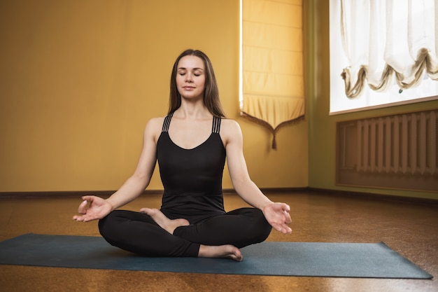 Young attractive woman in black sportswear practicing yoga is engaged in meditation in the lotus position on a gymnastic mat in the studio