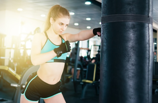 Young attractive woman boxing and training her punch with punching bag in the gym