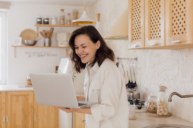 A young attractive woman in a bright modern kitchen uses a laptop for video communication