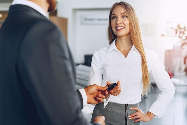 Молодая привлекательная женщина покупает новую машину в автомобильном салоне крупным планом