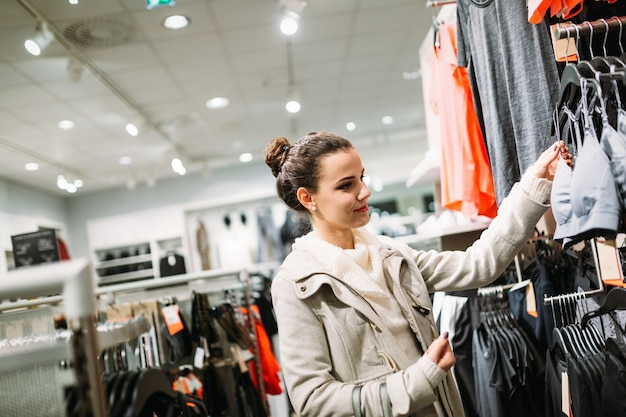 Молодая привлекательная женщина покупает одежду в торговом центре