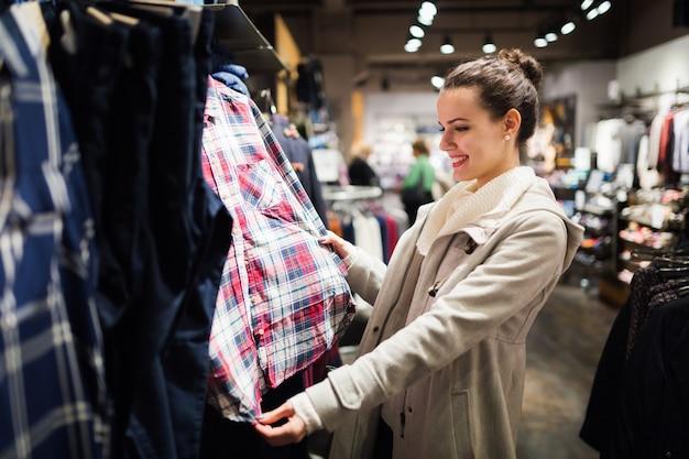 쇼핑몰에서 옷을 사는 젊은 매력적인 여자