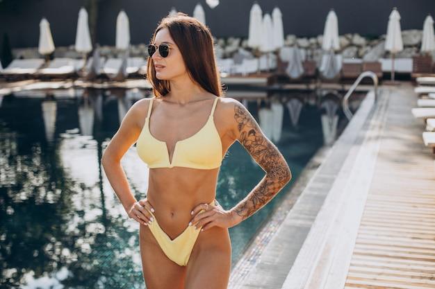 Молодая привлекательная женщина у бассейна