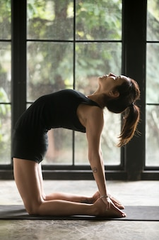 Young attractive woman in camel pose, home background
