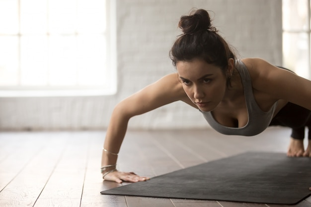 Young attractive woman in chaturanga dandasana pose, white loft