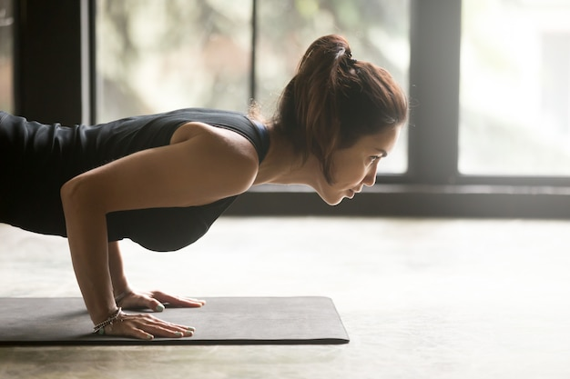 Young attractive woman in chaturanga dandasana pose