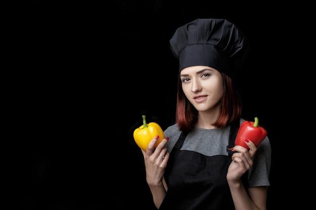 黒の制服を着た若い魅力的な女性シェフは、黒の背景にピーマンを保持します。
