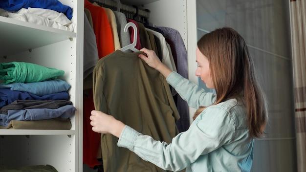 Молодая привлекательная женщина выбирает одежду в шкафу дома.