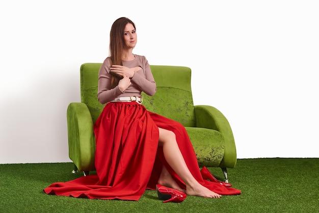 Молодая привлекательная женщина расчесывает волосы, сидя на диване в студии и снимая обувь во время отдыха между съемками