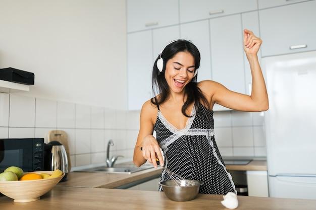 Молодая привлекательная женщина готовит яичницу на кухне утром, улыбается, счастливая позитивная домохозяйка, здоровый образ жизни, слушает музыку в наушниках, смеется, веселится, танцует, поет