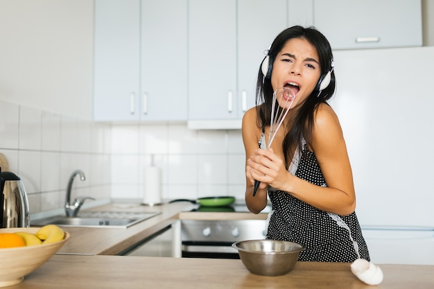Giovane donna attraente che cucina uova strapazzate in cucina al mattino, sorridente, casalinga positiva felice, sana, ascoltando musica in cuffia, cantando con la frusta come nel microfono, divertendosi