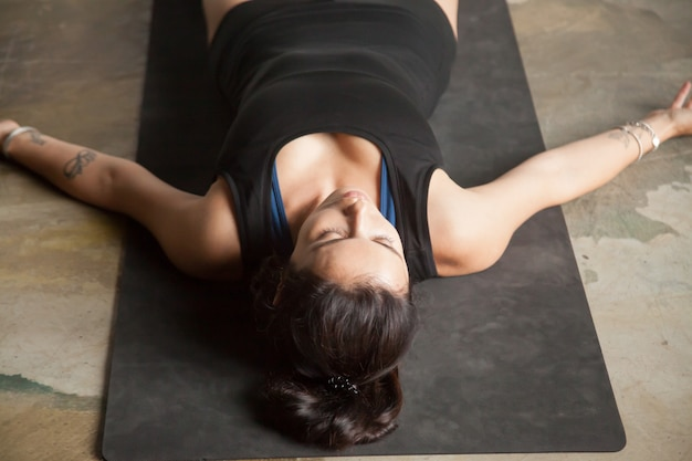 Young attractive woman in corpse pose, studio floor background