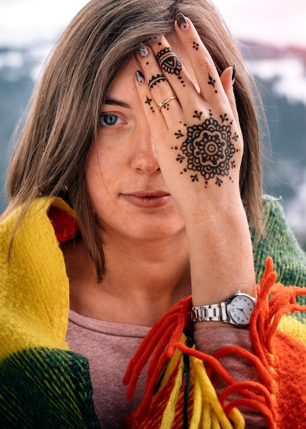 young attractive woman covering eye with mehndi hand