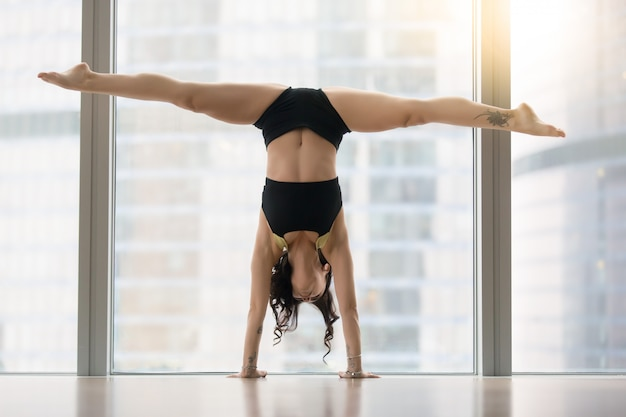 Young attractive woman in dance pose against floor window