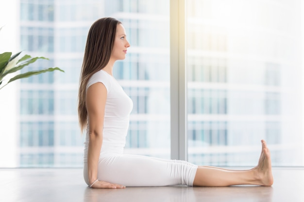 Young attractive woman in dandasana pose against floor window