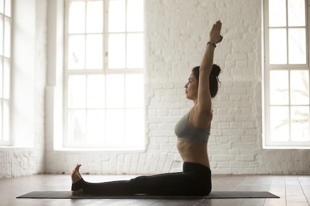 Young attractive woman in dandasana pose, white loft studio