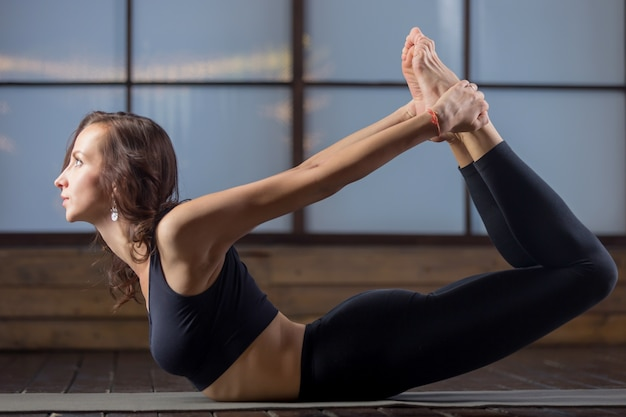 Young attractive woman in the dhanurasana pose, studio evening p