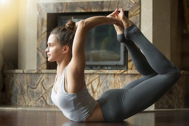 Young attractive woman in dhanurasana pose