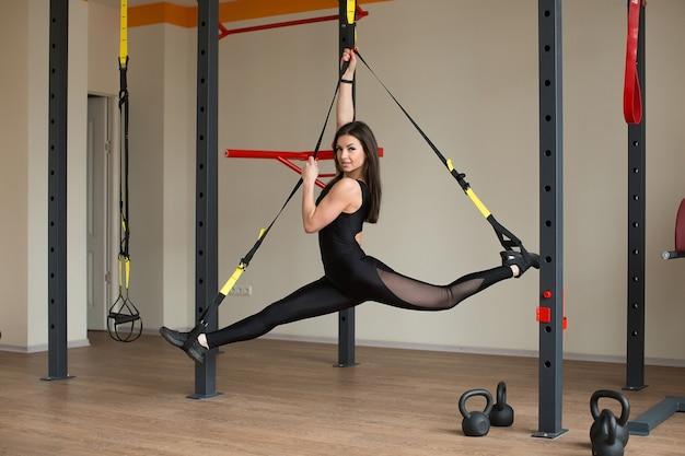 Молодая привлекательная женщина делает кроссфит-растяжку с ремнями для фитнеса trx в студии тренажерного зала