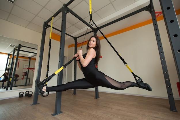 Молодая привлекательная женщина делает кроссфит растяжку