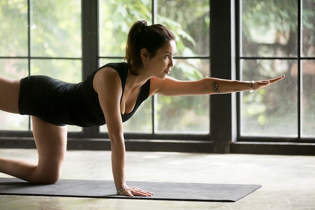 Young attractive woman doing donkey kick exercise