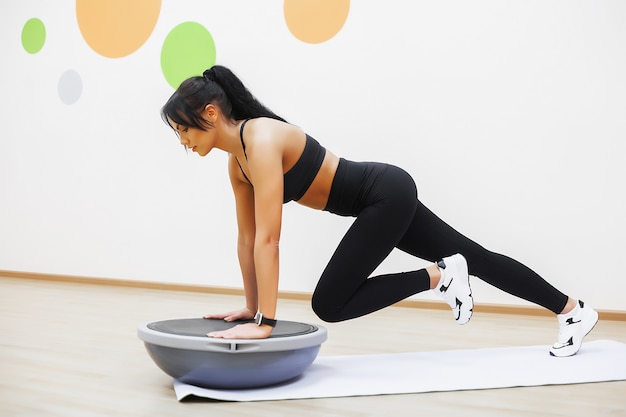 Young attractive woman doing exercises in fitness gym