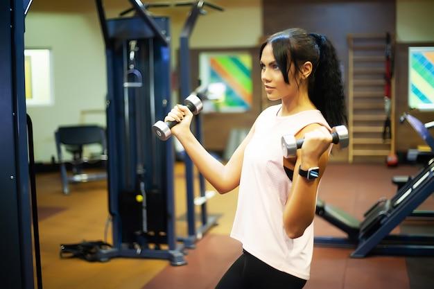 フィットネスジムでの演習を行う若い魅力的な女性。