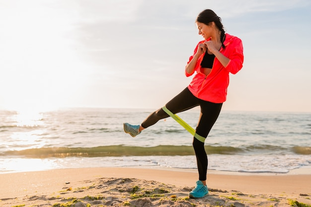 海のビーチで朝の日の出、健康的なライフスタイル、イヤホンで音楽を聴く、ピンクのウインドブレーカージャケットを着て、輪ゴムでストレッチをするスポーツ運動をしている若い魅力的な女性