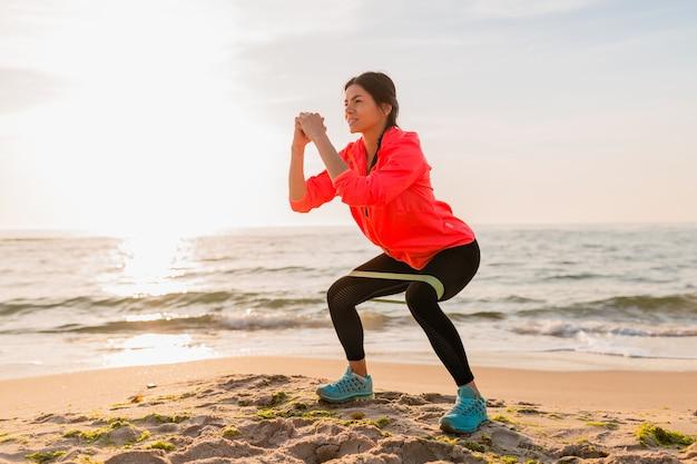 Молодая привлекательная женщина делает спортивные упражнения в утреннем восходе солнца на морском пляже, здоровый образ жизни, слушает музыку в наушниках, носит розовую куртку-ветровку, делает растяжку в резинке