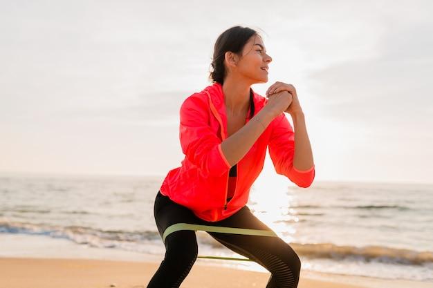 바다 해변에서 아침 일출에 스포츠 운동을하는 젊은 매력적인 여자, 건강한 라이프 스타일, 이어폰으로 음악 듣기, 핑크 윈드 재킷을 입고 고무 밴드에서 스트레칭 만들기