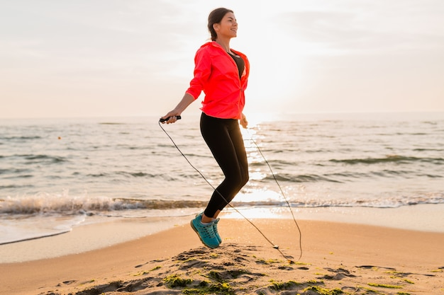 Молодая привлекательная женщина делает спортивные упражнения в утреннем восходе солнца на морском пляже в спортивной одежде, здоровом образе жизни, слушает музыку в наушниках, в розовой ветровке, прыгает в скакалке