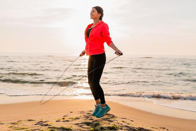 스포츠 착용, 건강한 라이프 스타일에 바다 해변에서 아침 일출에 스포츠 운동을하는 젊은 매력적인 여자, 이어폰에서 음악을 듣고, 핑크 윈드 재킷을 입고, 점프 로프에서 점프