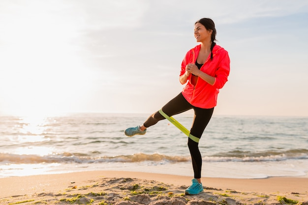Young attractive woman doing sport exercises in morning sunrise on sea beach, healthy lifestyle, listening to music on earphones, wearing pink windbreaker jacket, making stretching in rubber band