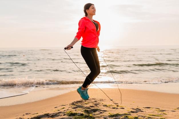 Giovane donna attraente che fa esercizi sportivi all'alba del mattino sulla spiaggia del mare in abbigliamento sportivo, stile di vita sano, ascolto di musica con gli auricolari, indossa una giacca a vento rosa, salta in corda per saltare