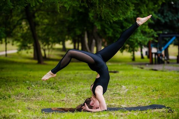 Молодая привлекательная женщина делает стойку на голове