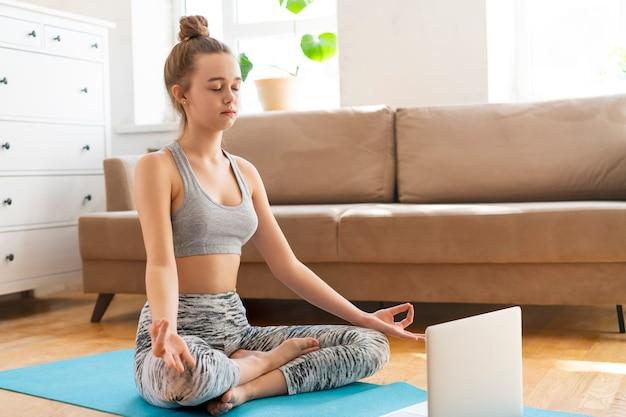 自宅でヨガの練習をしている若い魅力的な女性自宅で蓮華座、アルダパドマサーナの練習、リビングルームで半分ロータスポーズ。スポーツウェアのブラとパンツを着てワークアウト。健康管理