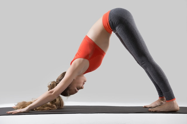 Young attractive woman in downward facing dog pose, grey studio