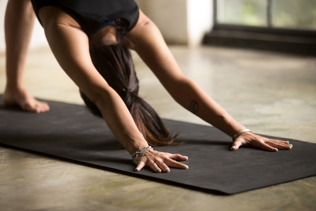 Young attractive woman in downward facing dog pose
