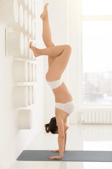 Young attractive woman in downward facing tree pose, white backg