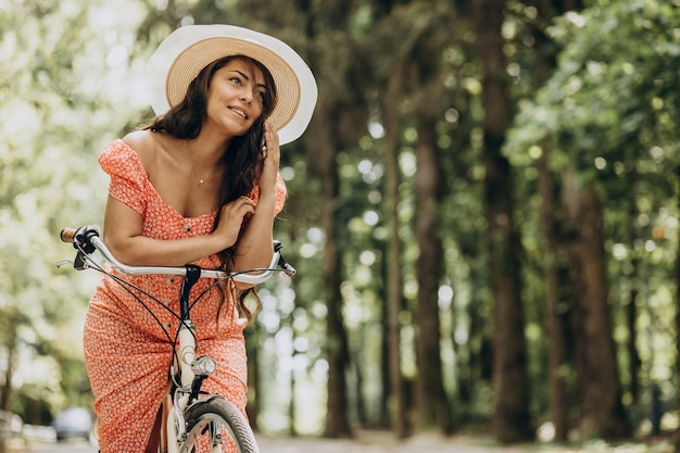 Young attractive woman in dress riding bicycle and using phone