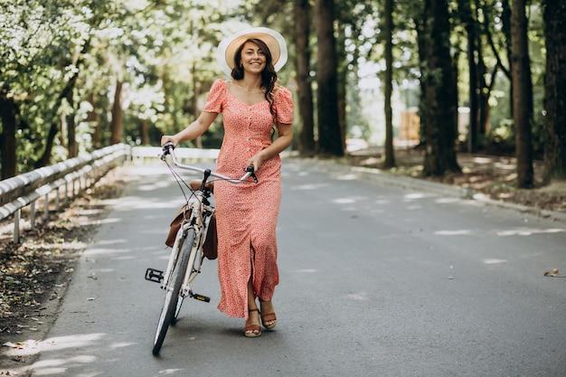 Giovane donna attraente in bicicletta di guida del vestito