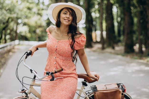 Young attractive woman in dress riding bicycle