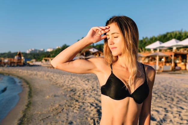 Giovane donna attraente vestita in costume da bagno nero sulla spiaggia di sabbia estiva