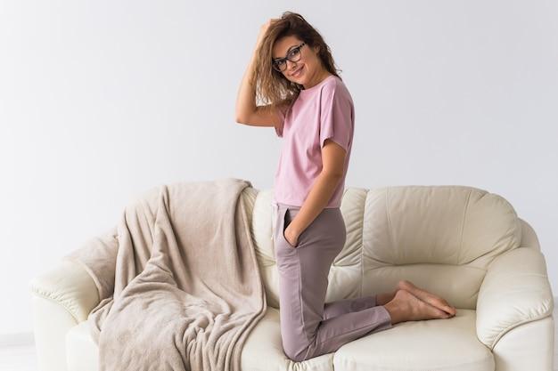 彼女のリビングルームでモデルを装った美しいカラフルなパジャマを着た若い魅力的な女性