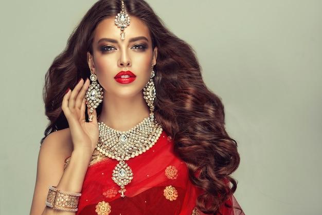 伝統的なインドの赤いショール(dupatta)に身を包み、手作りの「クンダンスタイル」のジュエリーセットに身を包んだ若い魅力的な女性。完璧で、密度が高く、波打つ、自由に飛ぶ髪と「スモーキーアイ」スタイルのメイク。