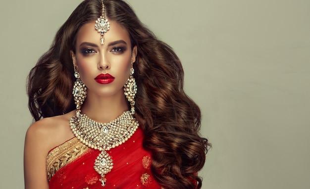 伝統的なインドの赤いショール(dupatta)と手作りの「クンダンスタイル」のジュエリーセットを身に着けた若い魅力的な女性。完璧で、密度が高く、波打つ、自由に飛ぶ髪と「スモーキーアイ」スタイルのメイク。
